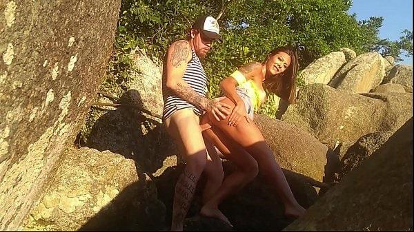 Sexo na praia com a morena tesuda demais da conta dando escondida no meio das pedras